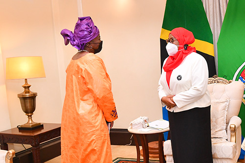 Two women in formal business attire stand apart, wearing face masks. Behind them are the national flag of the United Republic of Tanzania and the flag of the president.