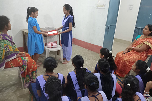 Two girls stand before a crowd of seated adolescent girls. They are holding a clean menstrual pad.