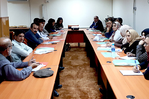 Women in headscarves and men in business attire sit around a conference table.