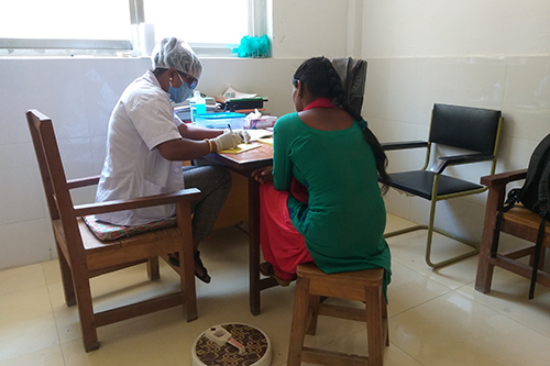 Kala Chaudhary, wearing a face mask, gloves and hair covering, sits at a desk and takes notes while providing a family planning consultation to a woman.