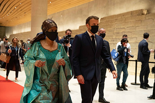 Phumzile Mlambo-Ngcuka and Emmanuel Macron walk into a convention hall. They are wearing face masks.