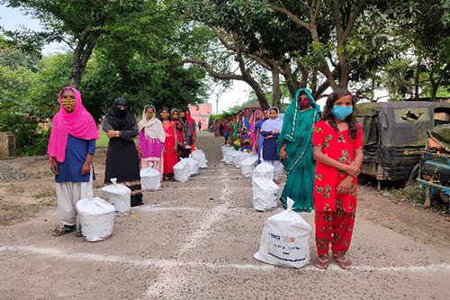 Women and girls wearing facemasks queue along a grid drawn in chalk on the ground to ensure physical distancing during the dignity kit distribution.