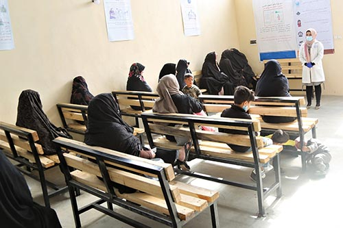 Women in head scarves sit on wooden benches. They are listening to a woman in a white medical coat wearing a face mask.