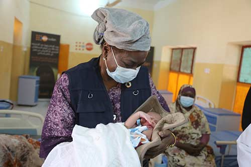 Executive Director Dr. Natalia Kanem holds a newborn baby in the Damazin maternity hospital.