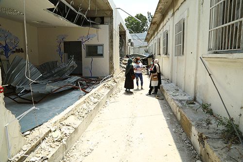 An assessment team stands in a destroyed part of a hospital in Karantina. Around them are rubble and exposed rebar.