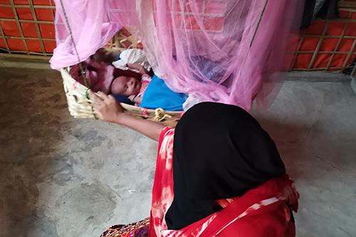 A woman wearing a black headscarf rocks a baby in a basket.