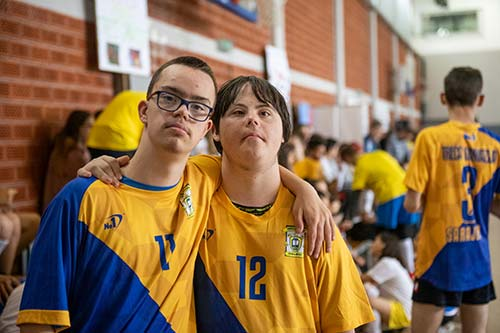 Two young men with disabilities are pictured participating in a sports activity.