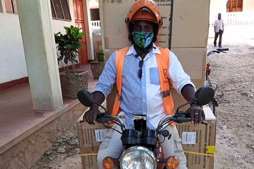 A SafeBoda driver prepares to drive away on a motorcycle carrying four large boxes of reproductive health cargo.