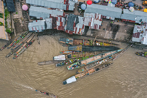 Boats are seen on a river, photographed from above.