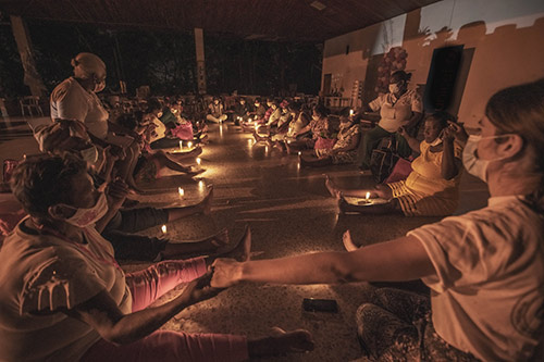 Pregnant women sit in a circle in a dimmed, candle-lit room, holding hands.