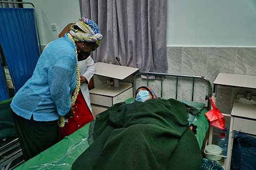 Dr. Kanem speaks to a woman lying on a bed at a maternity ward. Both are wearing face masks.