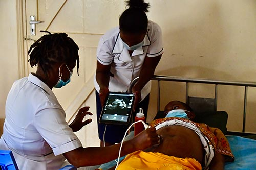 Two midwives in face masks and white uniforms perform an ultrasound on a pregnant woman, who is also wearing a face mask.