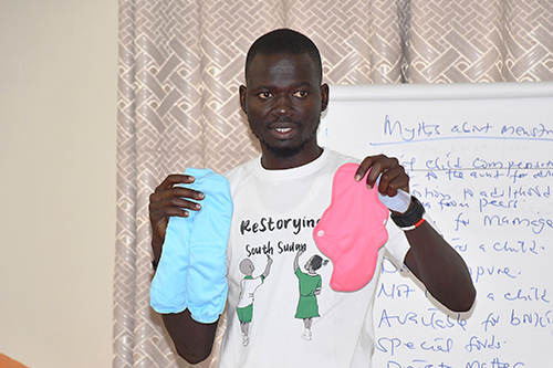 Data Gordon holds up reusable menstrual pads as he speaks to a group of men about menstruation myths.