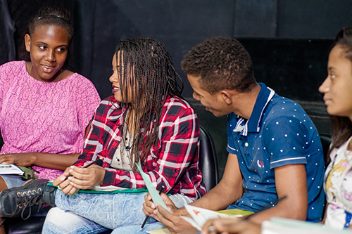 Young people in Brazil sit in a row and speak to one another about papers they are holding.