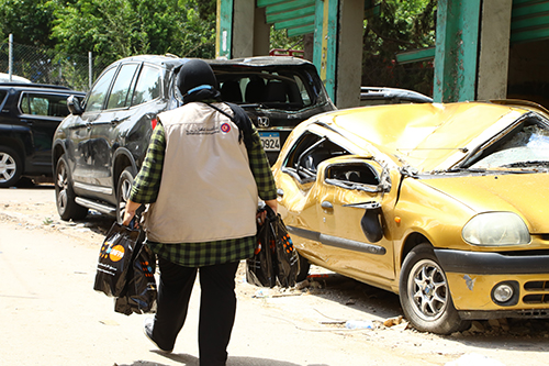Hiba Kchour carries bags of hygiene supplies past a crushed yellow car.