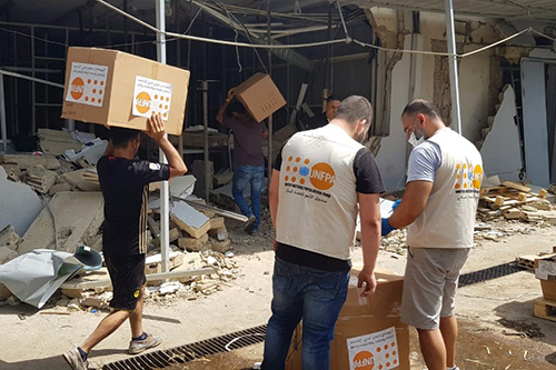 UNFPA staff members carry boxes of PPE over rubble.