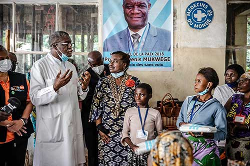A tall doctor in a white coat speaks with UN personnel and other people.