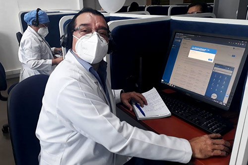 A doctor wearing a face mask sits at a computer.