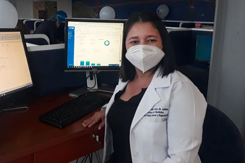 A doctor wearing a face mask sits at a computer with two monitors.