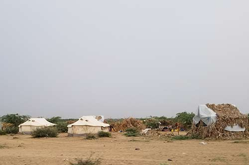 Three tents stand on a sandy ground. One on the left is covered in thatch.