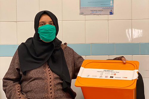 A pregnant woman wearing a face mask sits in a health centre with her SALAMA kit, which contains supplies and information to help prevent COVID-19 transmission.