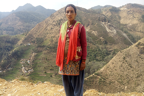 Hira stands against a cliff side, with tall mountains and terraced fields behind her.