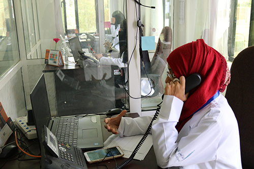 A woman in a red hijab takes a phone call at a UNFPA-supported mental health care hotline.