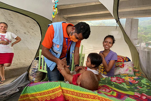 A doctor wearing a UNFPA vest checks up on an infant, who is lying on an air mattress inside a tent.