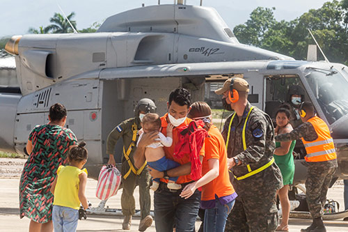 Families are assisted by humanitarian workers using a helicopter.
