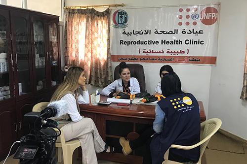 Dashni Murad sits with UNFPA staff in a reproductive health clinic. They are being filmed as they interact.