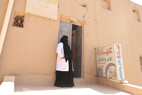 A health worker in a black veil and white lab coat stands outside a clinic.