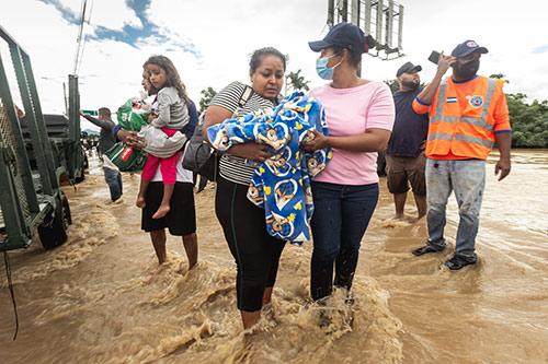 Women carry their children through ankle-deep flood water.