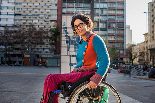 A woman in a wheelchair smiles at the camera.