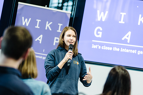 Nataliia Koshovska speaks to a group of  young people. She is holding a microphone and wearing a sweatshirt with the UNFPA logo.