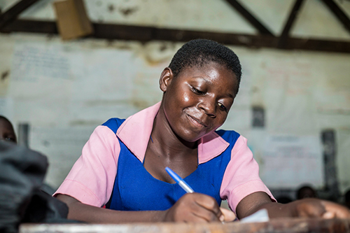 Laureen smiles while writing at a school desk.
