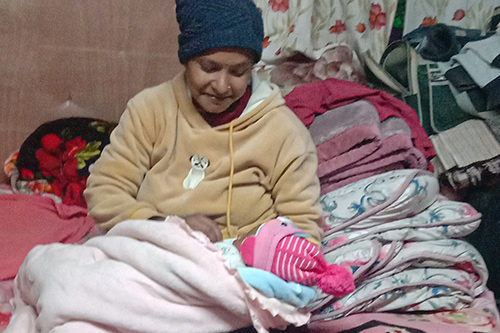 Maya holds her newborn baby girl. Maya is wearing a blue had and her baby is bundled in pink blankets.