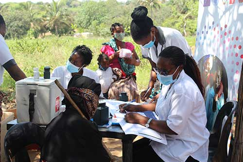 Health workers in face masks speak with patients at an outdoor table. They are part of a mobile clinic.
