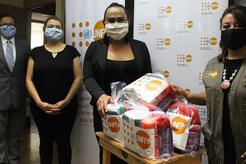 UNFPA staff stand beside kits intended for delivery to key populations.