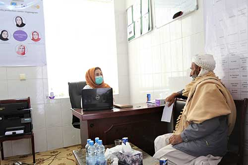 Dr. Freshta Fahim, wearing an orange head scarf and face mask, speaks to Aref, wearing a brown shawl.