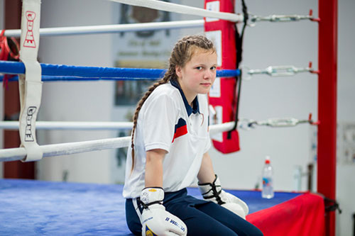 A girl in boxing gloves poses on a boxing ring.