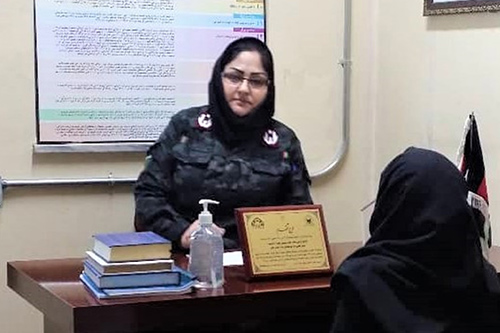 Palwasha Talash, wearing a headscarf and tinted glasses, sits at a desk. A woman in a headscarf sits on the other side of the desk.