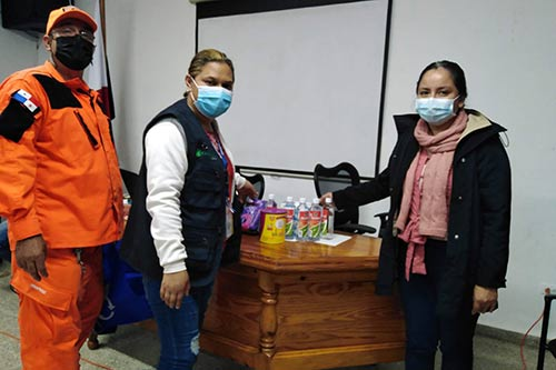 Individuals wearing face masks prepare kits with essential supplies.