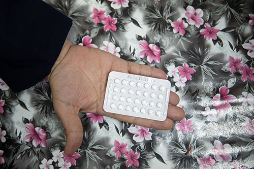 A woman's hand holds a pack of oral contraceptive pills.