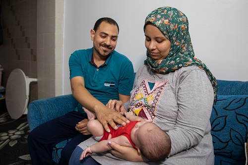 Ms. Reda with her husband and newborn son.