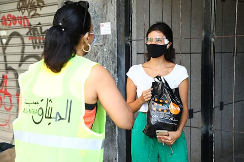 Rima passes a dignity kit to a young woman with a bandage on her face.