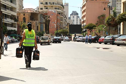 A field worker carries dignity kits through the streets of Beirut.