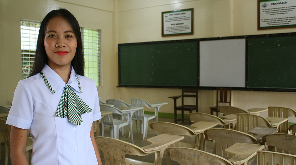 Shaina, a girls' advocate in the Philippines, stands in an empty classroom.