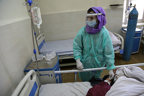 Midwife Suhaila checks on a patient. She is wearing a face mask, face shield, gloves and protective gown.