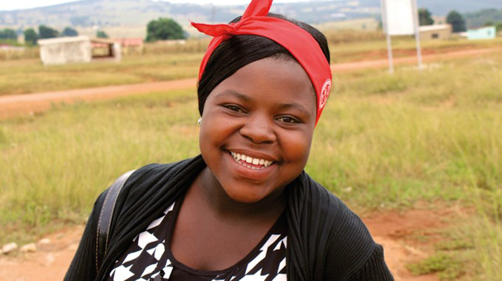 Takhona stands in a field in Eswatini. She is smiling broadly.