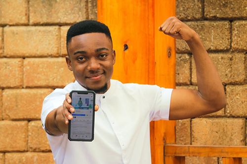 A young man shows off an app on his mobile phone with one hand, and flexes the bicep of his other arm.